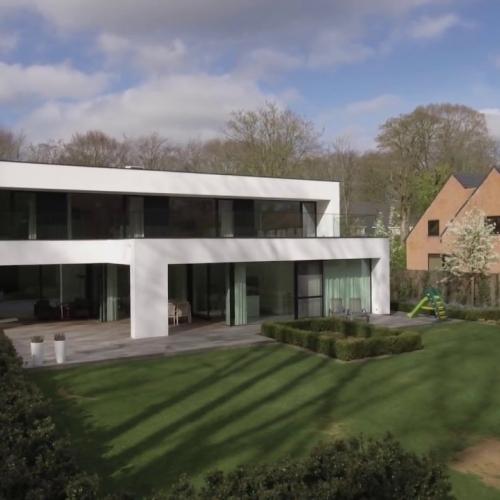 strakke witte woning in groene omgeving